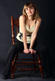 Girl sitting on a chair. Young beautiful women sitting on a chair royalty free stock photography