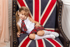 Girl sitting on chair with a British flag Stock Photography