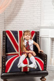 Girl sitting on chair with a British flag Stock Photos