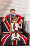 Girl sitting on chair with a British flag Royalty Free Stock Photography