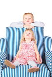 Girl is sitting on chair. brother is behind Stock Photography