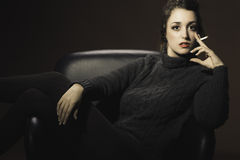 Woman sitting in a chair with cigarette royalty free stock images