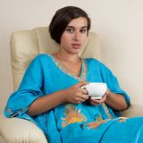 Girl sitting in chair with cup. Girl in blue indian dress sitting in chair with cup Stock Photos