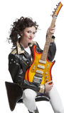 Girl sitting on the chair with electro guitar Stock Photos