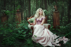 Girl sitting on a chair in the forest. Girl in evening dress sits on a an armchair in the fairy forest Royalty Free Stock Photos