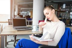 Girl is sitting in chair in her office and talking on the phone. She has a phone meeting. Young woman is concentrated. And serious Stock Photo