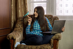 Girl sitting in chair with laptop and holding on the finger budg Stock Images
