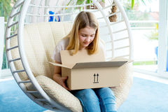 Girl sitting in chair and opening a package Stock Image