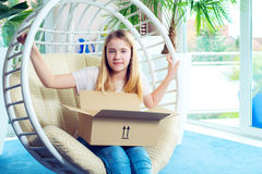 Girl sitting in chair and opening a package Stock Photography