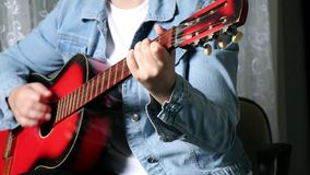 GIRL IS SITTING ON A CHAIR AND IS PLAYING A RED ACOUSTIC GUITAR. Female sitting on a chair in a room and playing a red acoustic vintage guitar stock video