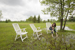 Girl Sitting on Chair in Rain Soaked Yard stock image