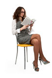 Girl is sitting on a chair and reading a book. Brunette girl is sitting on a yellow chair and reading a book on white background Stock Images