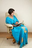 Girl sitting in chair reading book. Young girl sitting in chair reading book Royalty Free Stock Photos