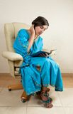 Girl sitting in chair reading book. Young girl sitting in chair reading book Stock Photos