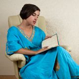 Girl sitting in chair reading book Royalty Free Stock Photography