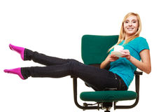 Girl sitting on chair relaxing holds cup of tea or coffee. Royalty Free Stock Photography