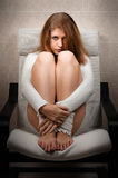 Girl sitting on chair in room Stock Photos