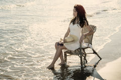 Girl sitting on a chair by the sea Stock Photography