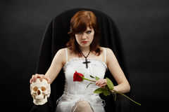 Girl sitting in chair with skull and rose. Young beautiful girl sitting in a chair with a skull and rose royalty free stock photo