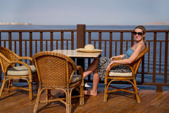 Girl sitting in a chair on the terrace by the sea Stock Photos