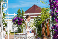 Girl sitting on chair under arch for wedding ceremony decorated Stock Photo