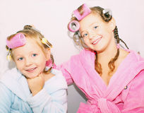 Girl sitting Childhood; Siblings. Two little sisters are in bath robes and home with curlers hairdo on the head. Isolated Royalty Free Stock Image