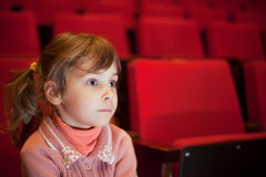 Girl sitting at cinema, steadfastly looking royalty free stock photos