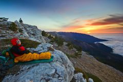 Girl sitting on a cliff in mountains at sunrise Stock Image