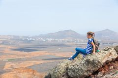 Girl sitting on cliff's edge, looking to a sky Stock Photos