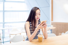 Girl sitting in a coffee shop Stock Image