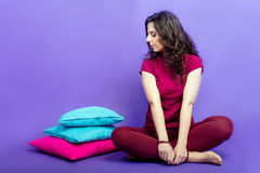 Girl sitting with colorful pillows on a purple background Stock Image