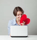 Girl sitting at a computer with a heart Royalty Free Stock Photography