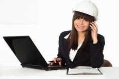 Girl sitting in the construction helmet Stock Photos