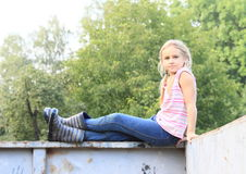 Girl sitting on a container Stock Images