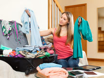 Girl sitting on couch with clothes in hands Stock Photography