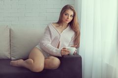Girl sitting on couch and holding a cup. Stock Image