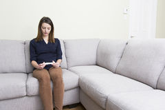 Girl sitting on a couch at home while reading the results of her recent pregnancy test Royalty Free Stock Images
