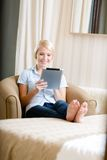 Girl sitting on the couch with silver pad Royalty Free Stock Photo