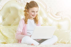Girl sitting on couch and using modern laptop Stock Photography