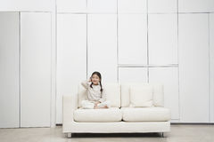 Girl Sitting Cross Legged On Sofa Royalty Free Stock Images