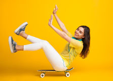 Girl sitting on cruiser riding in studio. Young woman sitting on skate with hands and legs up riding in studio on yellow background Royalty Free Stock Images