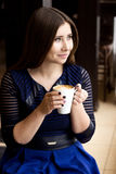 Girl sitting with a cup of coffee. In a blue dress and looking out the window Stock Photo