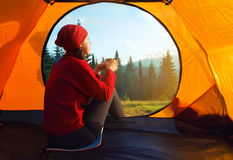 Girl sitting with cup inside orange tent looking at beautiful su Royalty Free Stock Image