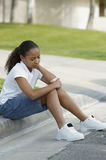 Girl Sitting On Curb. An upset African American girl sitting on curb at park Stock Photography