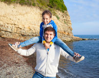 Girl sitting on dad's shoulders on sea background Royalty Free Stock Photos
