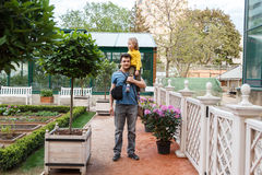 Girl sitting on Daddy shoulders in garden Royalty Free Stock Images
