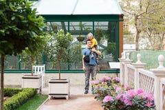Girl sitting on Daddy shoulders in garden Stock Photos