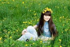 Girl sitting among dandelions Stock Photo