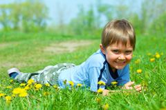 Girl sitting among dandelions Stock Photos