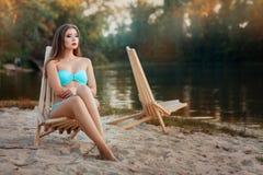 Girl is sitting deck chair beach near the lake. Stock Photos